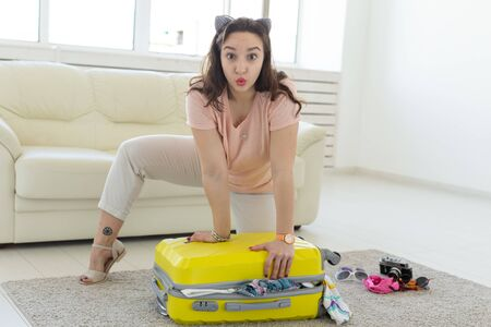 Vacation, travel and holidays concept - Young charming woman packing suitcase on background