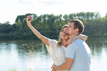 Capturing bright moments. Joyful young loving couple making selfie on camera while standing outdoors Stock Photo