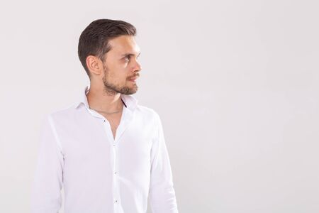 Portrait of handsome happy young man in casual shirt standing against white background with copyspace