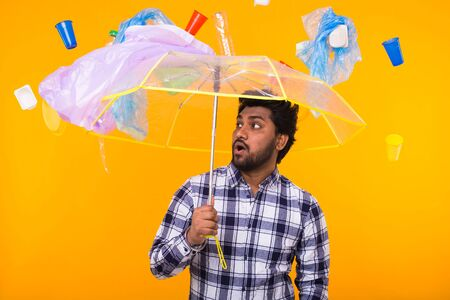 Environmental pollution, plastic recycling problem and ecology problem concept - Scared Indian man is standing under trash with umbrella on yellow background