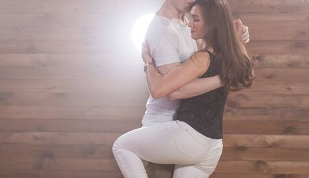 Social dance, bachata, kizomba, tango, salsa, people concept - Close-up of young couple dancing over wooden background with copy space
