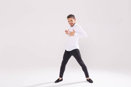 Handsome young man dancing on white background with copy space