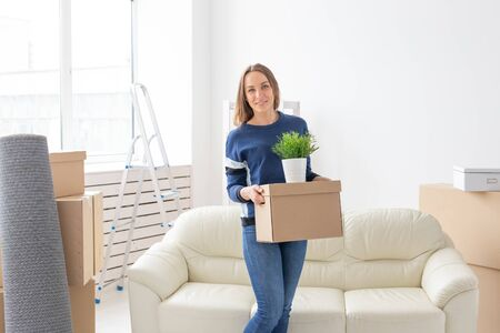 Charming young single woman holds a box with things while moving while standing in a new apartment next to her gray lop-eared scottish cat. The concept of moving and housewarming.