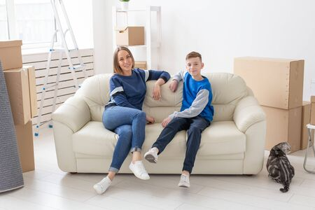 Satisfied happy caucasian single mother and son happily communicate discussing the design of the new apartment during the housewarming party with their scottish fold cat.