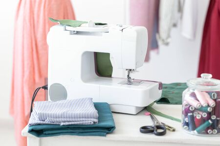 Designers desk sewing machine thread fabric scissors against the background of finished stitched products. Concept of tailoring to order