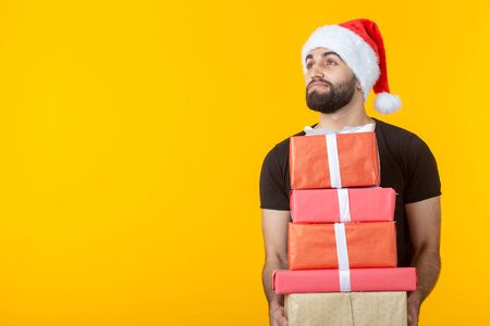 Disgruntled young man with a beard in a Santa Claus hat holds five gift boxes posing on a yellow background with copyspace. Concept of gifts and greetings for Christmas and New Year. Imagens