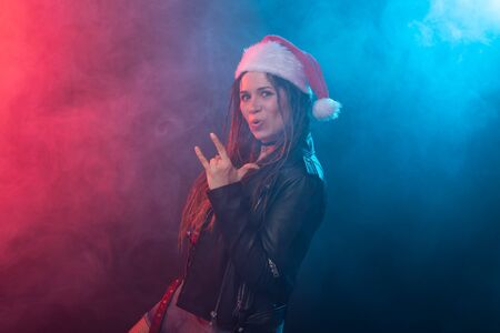 Rock, christmas and holidays concept - emotional woman in santa hat shows tongue and rock