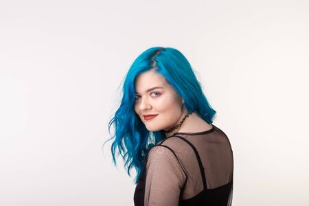 People and fashion concept - Beautiful woman with blue hair posing over white background