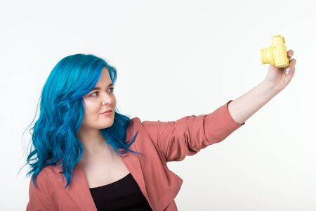 People, hobby and interests concept - Beautiful girl with blue hair hold yellow retro camera on white background