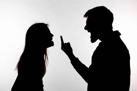 Concepto de agresión y abuso - hombre y mujer que expresan violencia doméstica en silueta de estudio aislado sobre fondo blanco.