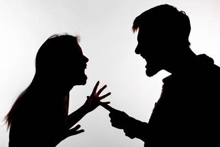 Concept d'agression et d'abus - homme et femme exprimant la violence domestique en silhouette de studio isolée sur fond blanc. Banque d'images