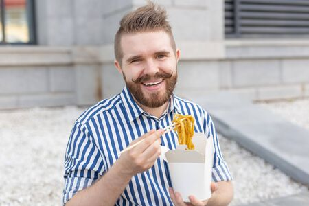 Close-up of an amusing young hipster guy eating chinese noodles with wooden chopsticks sitting in a park outside on a warm summer day. The concept of rest and snacking on the street.