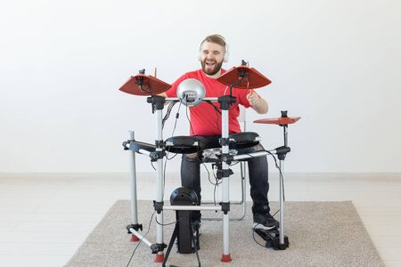 People, free time and hobby concept - bearded man drummer playing the drum.