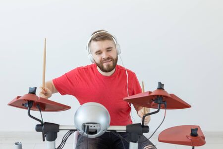 Emotions, electronic drums and people concept - young man drummer playing the drum