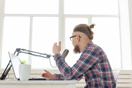 blogger, streamer and broadcasting concept - young man DJ working on the radio.