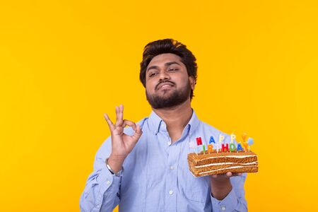 Positive funny young indian guy with a cap and a homemade cake in his hands posing on a yellow background. Anniversary and birthday concept.