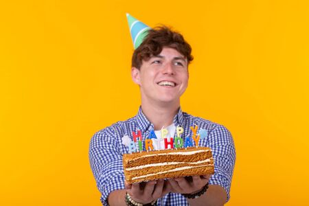 Crazy cheerful young man in paper congratulatory hat holding cakes happy birthday standing on a yellow background. Jubilee congratulations concept.