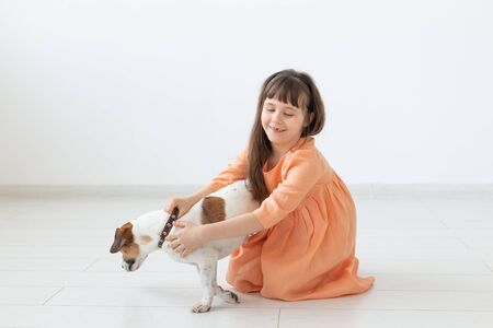 Little charming girl with dark hair in a long dress is sitting next to the dog Jack Russell Terrier on the floor of her room. The concept of child innocence and child care. Copyspace.