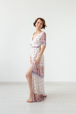 Clothing designer and people concept - woman in floor-length dress over the white background