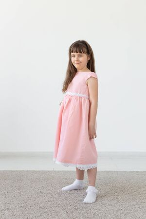 Beautiful little brunette girl in a pink dress posing on a white background. The concept of cute children. Copy space