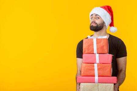 Disgruntled young man with a beard in a Santa hat holds five gift boxes posing on a yellow background with copyspace. Concept of gifts and greetings for Christmas and New Year. Imagens