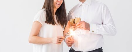 New year, holidays, date and valentines day concept - Loving couple holding sparklers light and glasses of champagne close-up over white background