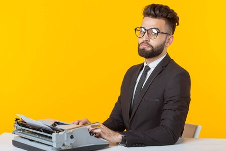 Arab businessman or manager in formal suit typing text on a typewriter on a yellow background. Concept of business and office work