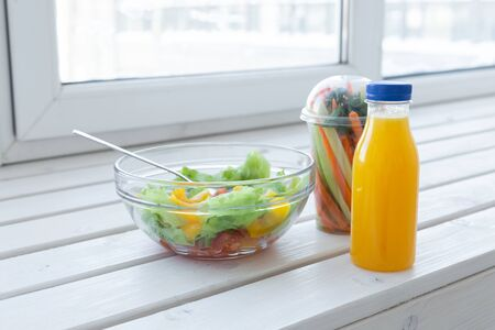Bowl of green salad, raw vegetables and bottle of orange juice. Weight loss, diet and right nutrition concept