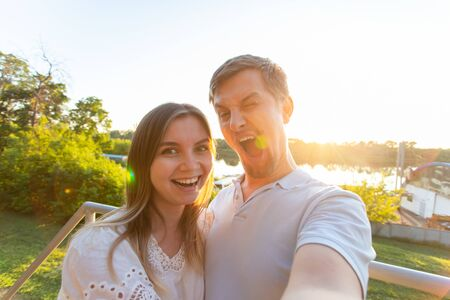 Capturing bright moments. Joyful young funny loving couple making selfie on camera while standing outdoors
