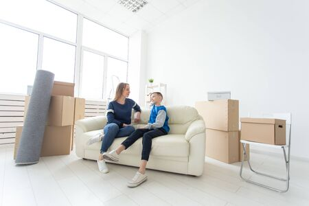 Cute single mom and little boy son relaxing after the move. The concept of housewarming mortgage and the joy of new housing. 版權商用圖片