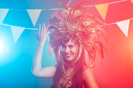 Carnival, dancer and holiday concept - Portrait of a female in a colorful sumptuous carnival feather suit. Nightlife of female dancer