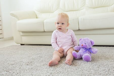 Children and childhood concept - Little baby girl sitting on the floor