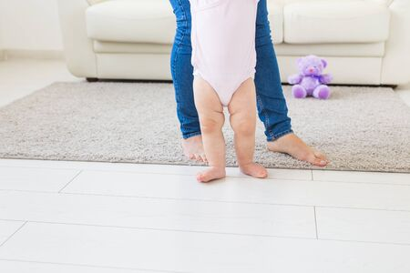 First steps of baby toddler learning to walk in white sunny living room. Footwear for child.