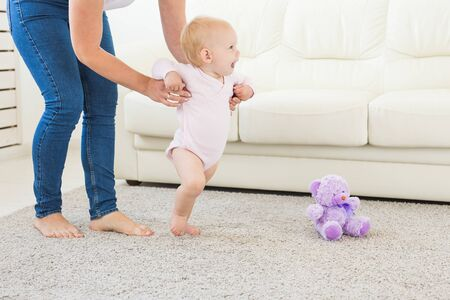 Little baby girl first steps with the help of mom Stock fotó