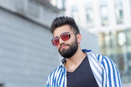 Portrait of handsome confidence man with a beard outdoors
