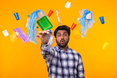 World Environment Day, plastic recycling problem and environmental disaster concept - surprised Indian man holding crumpled plastic bottle on yellow background. He is worried about ecology