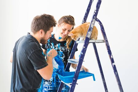 People, redecoration and relationship concept - Young funny couple with cat doing renovation in new apartment