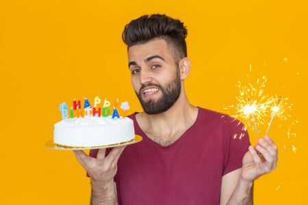 Crazy cheerful young guy holding a burning candle in his hands and a congratulatory homemade cake on a yellow background. Birthday and anniversary celebration concept.