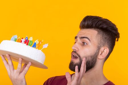 Embarrassed young male hipster with beard holding a birthday cake in his hands and looking thoughtfully at him posing on a yellow background. Concept of time quickly flies by.