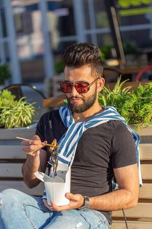 Handsome arab young hipster guy eating chinese noodles with wooden chopsticks sitting in a park outside on a warm summer day. The concept of rest and snacking on the street.