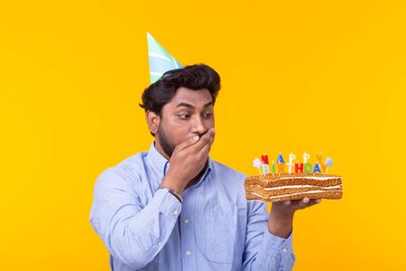 Portrait of a funny positive guy with a paper cap and glasses holding a congratulatory cake in his hands on a yellow background. Concept and fun and celebration. Advertising space.