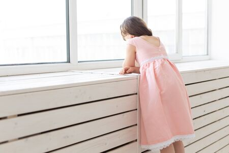 Dreamy little girl in a pink dress looks out the window