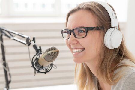 Radio host concept - Close-up portrait of woman radio presenter with headphones