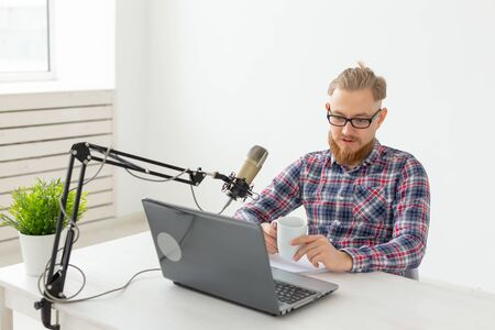 Radio host, streamer and blogger concept - Handsome man working as radio host at radio station sitting in front of microphone