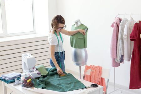 Young pretty girl seamstress designer with glasses and a measuring tape makes a new product with the help of a green cloth and a tailors dummy. Concept of sewing workshop. Reklamní fotografie