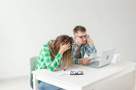 Upset husband and wife consider the total costs of payments and purchases made over the past month. The concept of low standard of living of students. Stock Photo