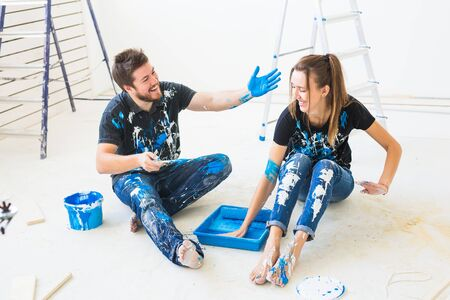 Renovation, redecoration and interiors concept - Young couple sitting on the white floor and pour paint and having fun