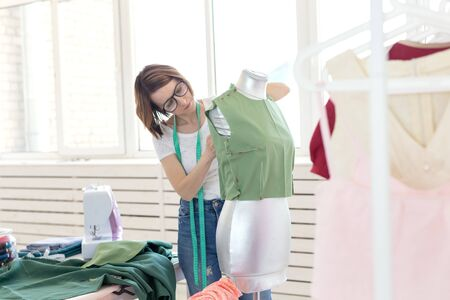 Pretty seamstress woman in glasses with a measuring tape makes a green blouse with the help of a tailors dummy and safety pins. Concept of own sewing workshop. Reklamní fotografie