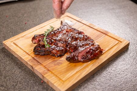 food, delicious and craft concept - cutting horse meat steak on wooden desk
