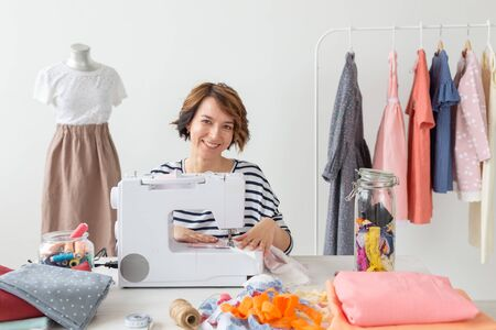 Concept of designer clothes. Woman seamstress working in studio